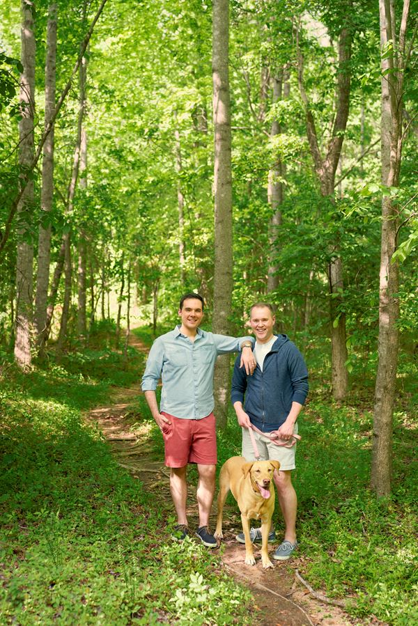 two men with a dog on a trail